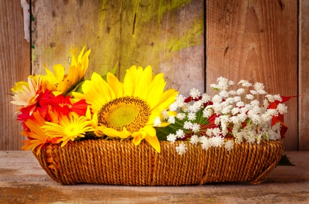 Sunflowers, daisies and  other flowers on a basket with a rustic wooden background photo
