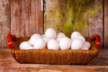 Eggs on a basket with a rustic old wood planks background photo