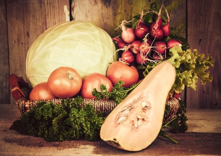 Vintage image of fruits and vegetables on a basket with a rustic background photo
