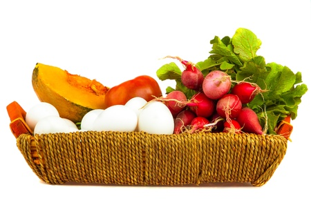 Vegetables and eggs on a basket isolated on a white background photo