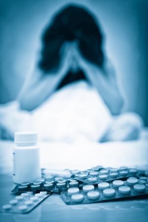 drogadiccion: Retrato azul entonado de una mujer deprimida con pastillas sobre la mesa