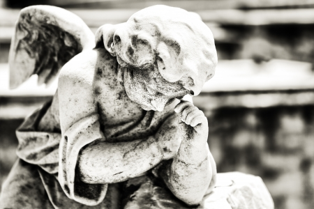 Black and white vintage image of a sad mourning angel on a cemetery with a diffused background photo