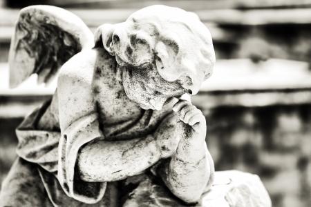 Zwart-wit uitstekend beeld van een trieste rouw engel op een begraafplaats met een diffuus achtergrond