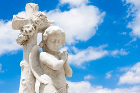 Mooie baby engel leunend op een christelijk kruis met een blauwe hemel achtergrond (met ruimte voor tekst) Stockfoto