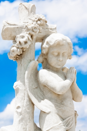 Beautiful infant angel leaning on a christian cross with a blue sky background (with space for text) photo