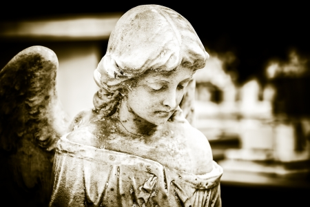 angel headstone: Vintage image of a sad angel on a cemetery with a diffused background Stock Photo