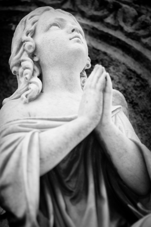 Black and white  image of an old angel sculpture praying and looking at the sky photo
