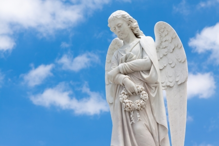 the angel of death: Beautiful white angel with a blue sky background (with space for text) Stock Photo