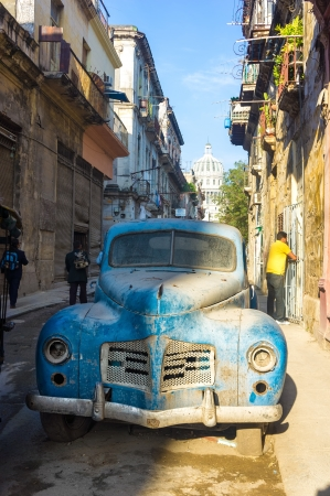 Street scene with an old rusty american car  in Havana These classic vintage cars that can be seen all over the country have become a worldwide known symbol of Cuba Stock Photo - 18928323