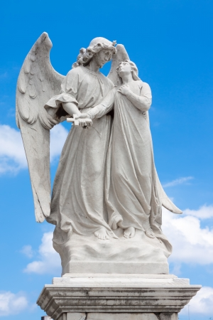 angel statue: Marble statue of a winged angel guarding a beautiful young girl