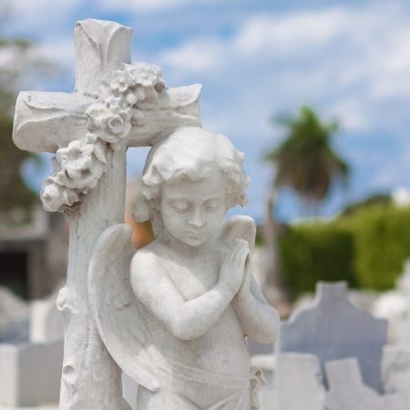 Infant angel praying and christian cross with a diffused cemetery background photo