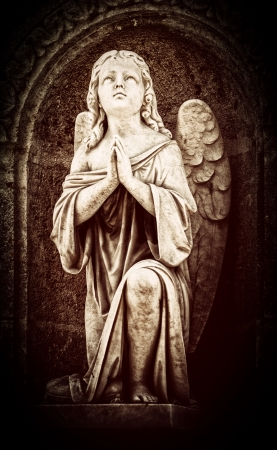 praying angel: Vintage image of an angel praying with a dark background Stock Photo