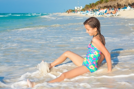 preteens beach: Cute hispanic teen playing with the waves on a beautiful beach in Cuba