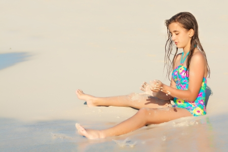preteens beach: Cute hispanic girl playing with sand on a sunny  beach