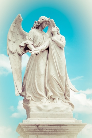 catholic angel: Marble statue of a winged angel guarding a beautiful young girl