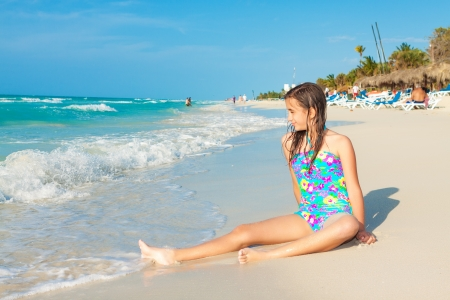 Cute hispanic teen playing with the waves on a beautiful beach in Cuba photo