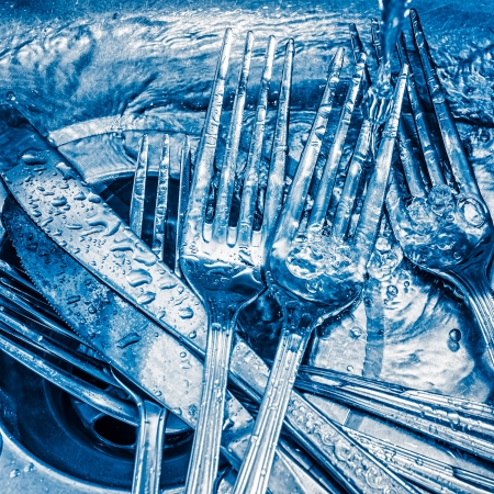 Blue toned image of forks and knives washed on a kitchen sink with a splash of water photo