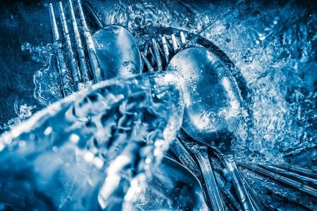 lavar platos: Imagen de tonos azul de plata metálica que se lava en un fregadero con un poco de agua