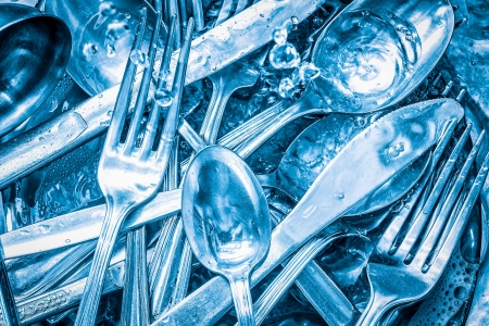 Blue toned silverware being washed with water and detergent photo