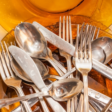 silver cutlery: Metallic silverware and glass dishes washed under a water stream Stock Photo
