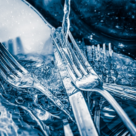 Blue toned image of forks and knives   washed on a sink with a splash of water photo
