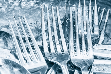 Forks and knives being washed under a water stream Stock Photo - 19296214