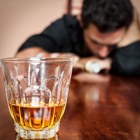alcoholismo: Retrato de un hombre borracho adicto al alcohol para dormir con la cabeza sobre la mesa