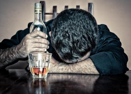 alcoholismo: Borracho deprimido con un vaso y una botella de dormir con la cabeza sobre una mesa