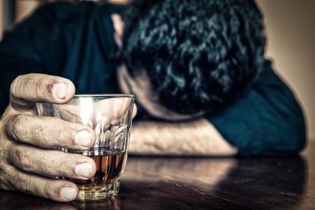 PrzygnÄ™biony pijany mężczyzna trzyma drinka i Å›pi z gÅ'owÄ… na stole koncentruje siÄ™ na drinka, a jego twarz jest nieostry Zdjęcie Seryjne