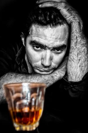 alcoholismo: Grunge retrato en blanco y negro de un hombre hispano borracho y deprimido con una contrastada bebida alcohólica de oro Foto de archivo