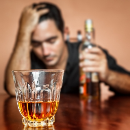 Drunk and lonely latin man holding a rum or whiskey bottle  image focused on his drink