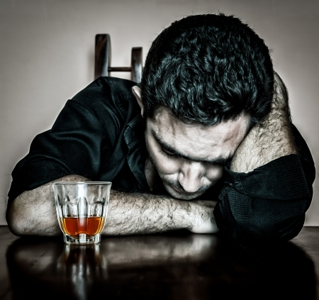 Alcoholism   Grunge bleached portrait of a lonely and desperate drunk hispanic man