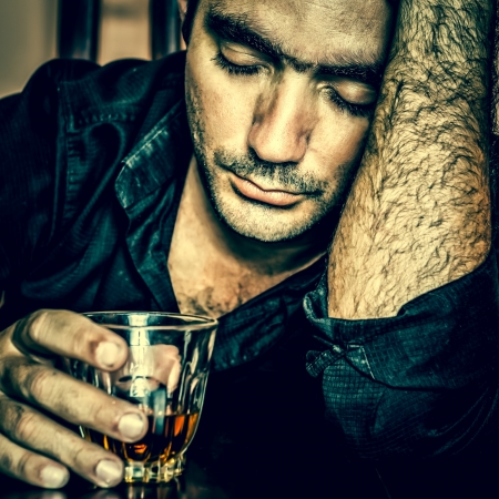 intoxicated: Alcoholism   Grunge blue toned portrait of a lonely and desperate drunk hispanic man