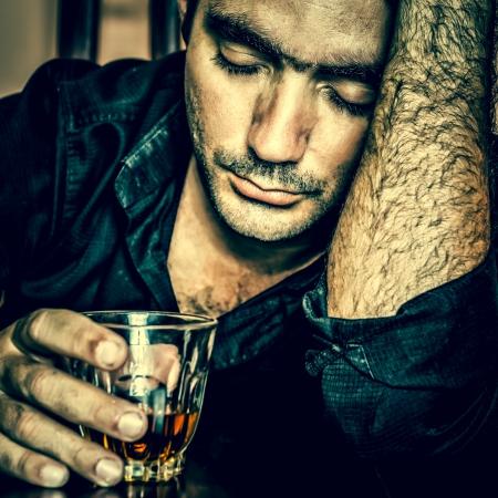 blue toned: Alcolismo Grunge blu tonica ritratto di un uomo ispanico ubriaco solo e disperato Archivio Fotografico