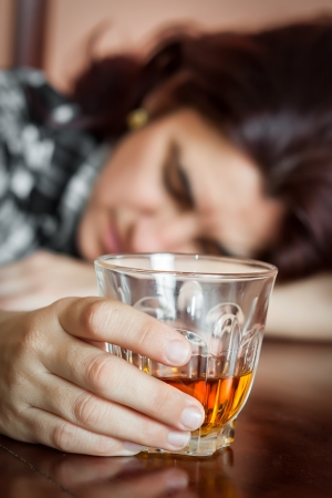 alcohol abuse: Alcohol abuse   Drunk hispanic woman holding a drink and slepping on a table