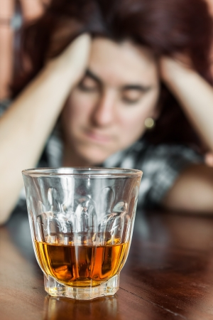 Alcohol addiction   Drunk and depressed hispanic woman  focused on her drink  Stock Photo - 19383252