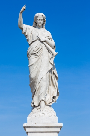 Religious statue of a young woman holding a trumpet and raising a finger as a judgement sign photo