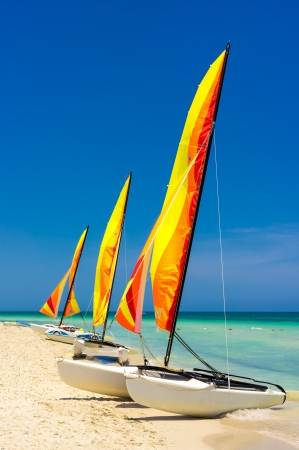 Three catamarans with their sails painted in bright colors at the shore of Varadero beach in Cuba photo