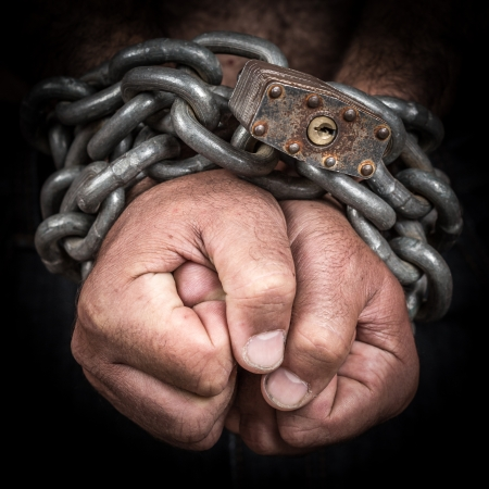 Close-up of two hands chained with an iron chain and a padlock  emerging from a black background