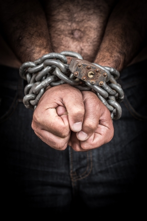 detained: Hands of a shirtless  man chained with an iron chain and a padlock  emerging from a black background