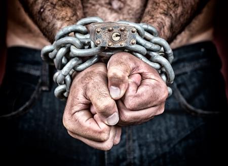 Dramatisch detail van de geketende handen van een volwassen man met een sterke ketting en hangslot