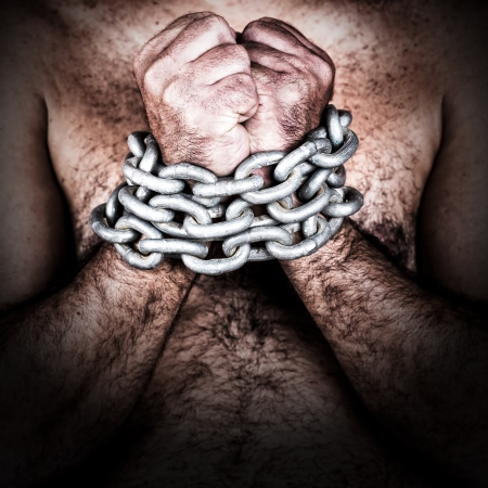 Dramatic detail of the chained hands of an adult shirtless man  with a strong chain and padlock  photo