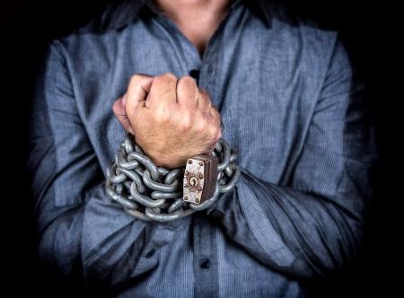 Handen van een formeel geklede man geketend met een ijzeren ketting en een hangslot op een zwarte achtergrond