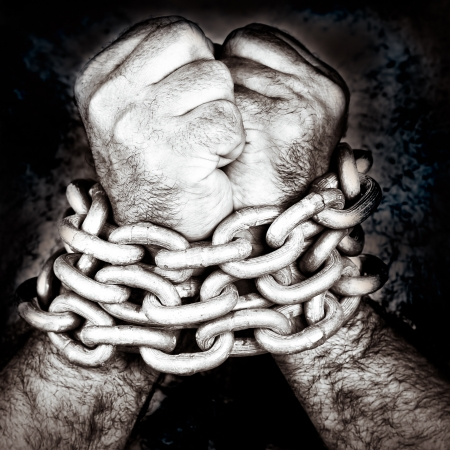 chained: Black and white grunge image of two hands locked by a strong steel chain Stock Photo