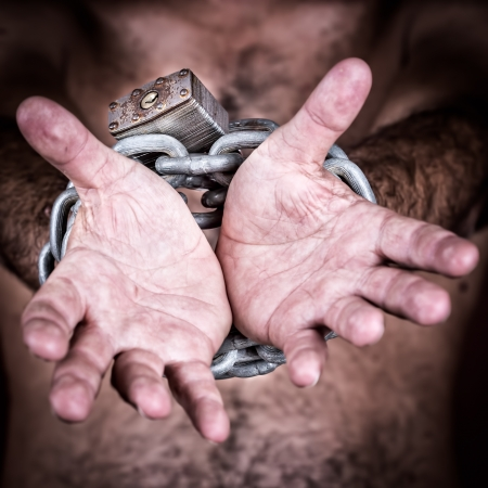 Chained hands gesturing to symbolize the need for freedom   in a dark background Stock Photo - 20179364