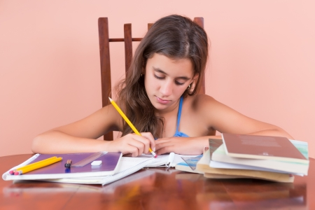 Cute hispanic girl working on her school homework photo