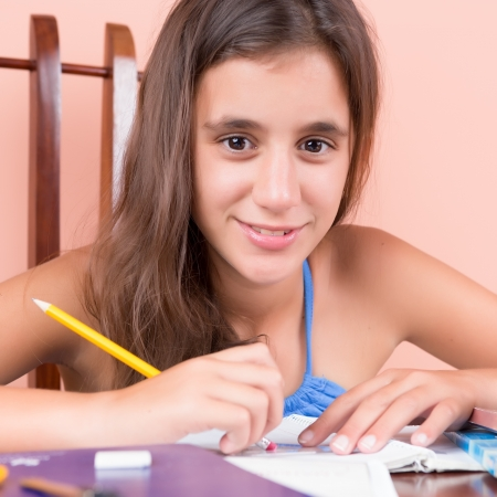 Hispanic girl studying at home and smiling photo