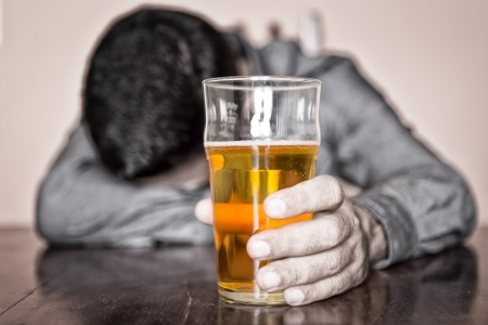 Black and white image of a sleeping drunk man  only his beer is in color