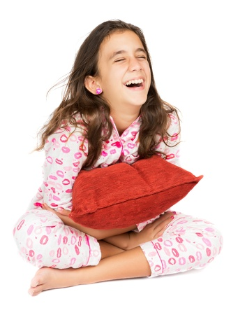 Hispanic teenager wearing pajamas laughing and hugging a red pillow  isolated on white  photo