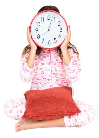 Child wearing pink pajamas holding a clock in place of her face  isolated on white  photo